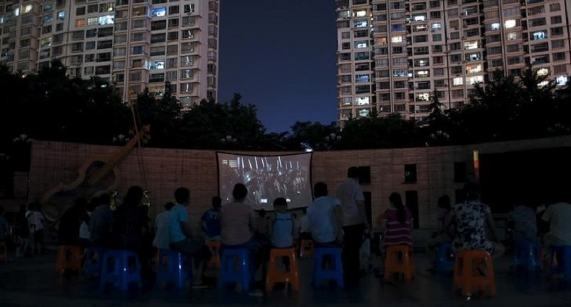 Residents watch a movie about the war against Japan during