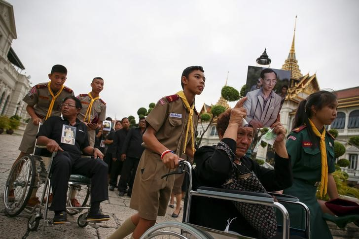 Mourners hold up pictures of Thailand's late King Bhumibol Adulayadej as they are pushed into the Throne Hall at the Grand Palace for the first time to pay respects to his body that is kept in a golden urn in Bangkok, Thailand, October 29, 2016. REUTERS/Athit Perawongmetha