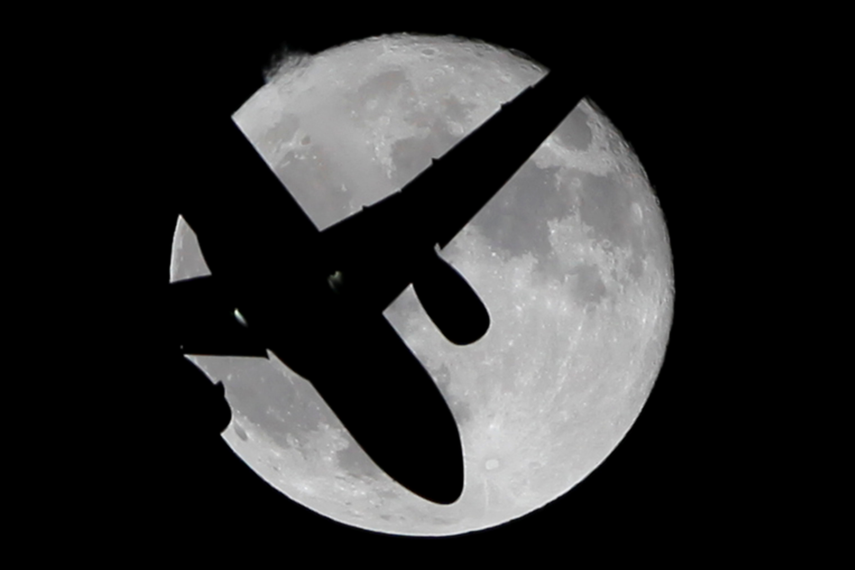 A Vueling passenger aircraft flies past a super moon in Ardales, southern Spain, October 17, 2016. REUTERS/Jon Nazca