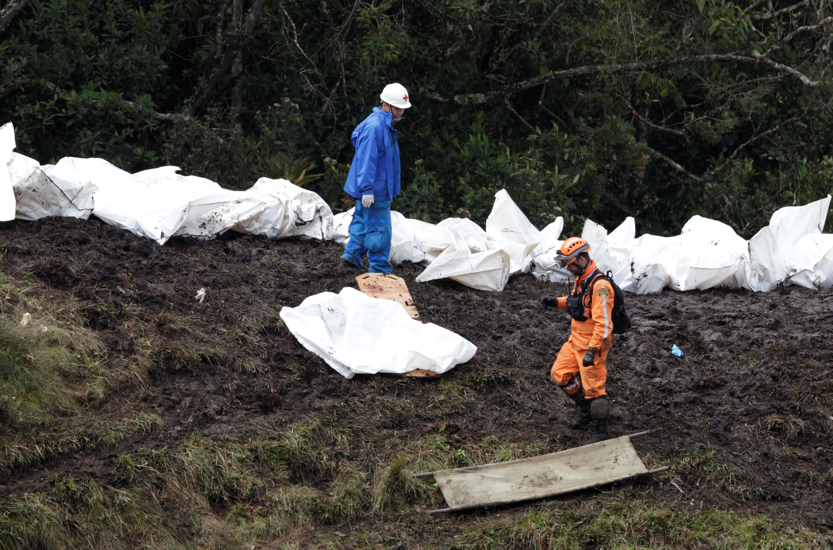Rescue workers walk next to bodies of victims from the wreckage of a plane that crashed into the Colombian jungle with Brazilian soccer team Chapecoense onboard near Medellin, Colombia, November 29, 2016.  REUTERS/Jaime Saldarriaga