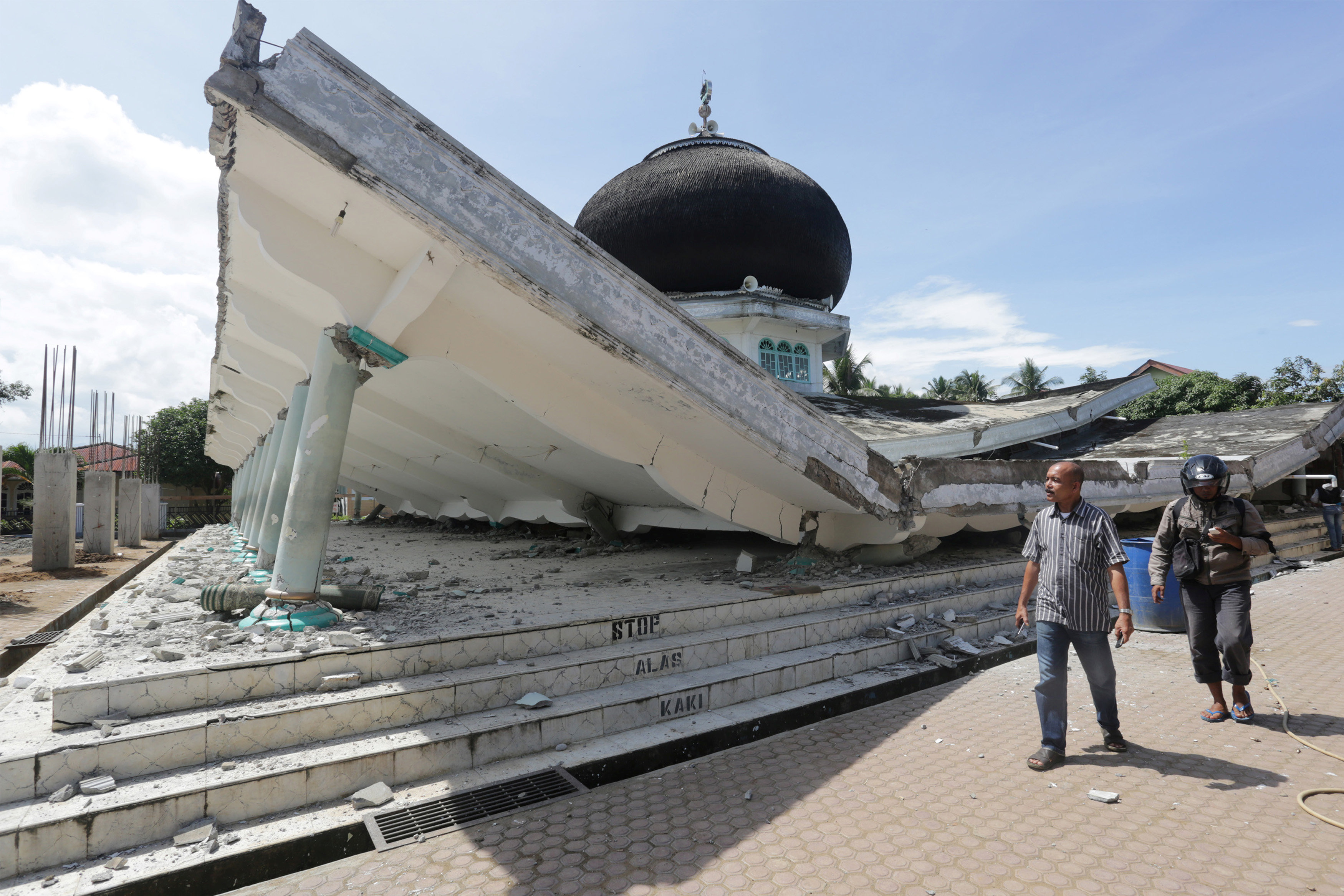 People walk near a collapsed mosque following an earthquake in Meuredu, Pidie Jaya in the northern province of Aceh, Indonesia December 7, 2016 in this photo taken by Antara Foto.  Antara Foto/ Irwansyah Putra/via REUTERS