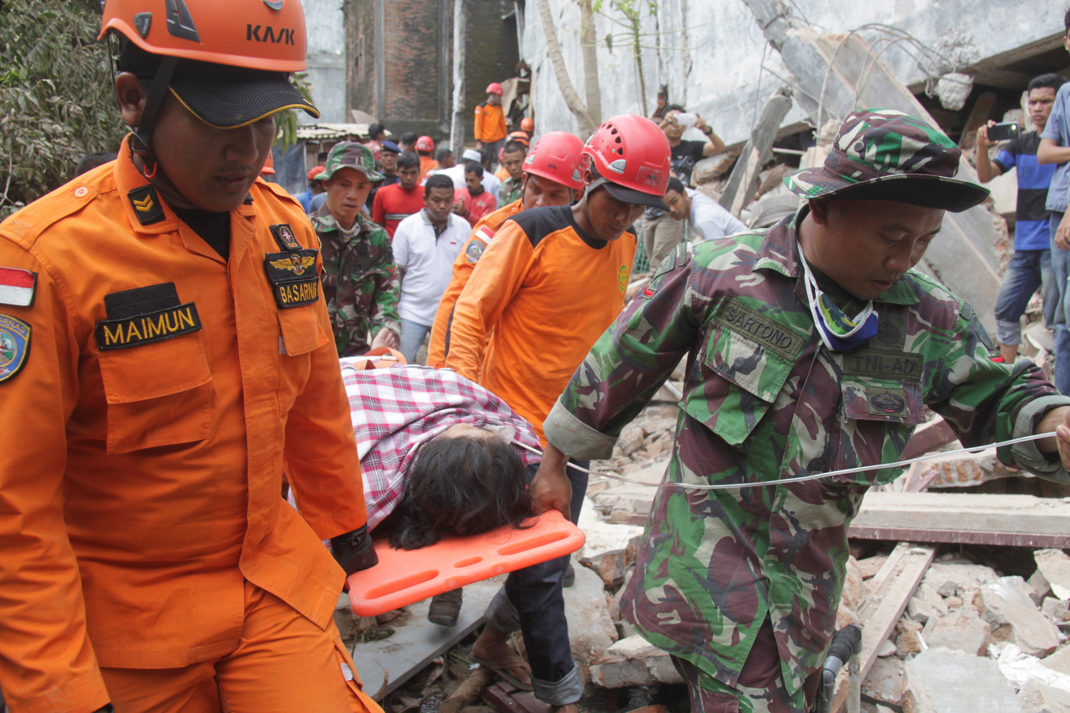 Indonesian rescue workers carry a survivor from a fallen building after an earthquake in Ulee Glee, Pidie Jaya, in the northern province of Aceh, Indonesia December 7, 2016. Antara Foto/Ampelsa/via REUTERS ATTENTION EDITORS - THIS IMAGE WAS PROVIDED BY A THIRD PARTY. FOR EDITORIAL USE ONLY. MANDATORY CREDIT. INDONESIA OUT.