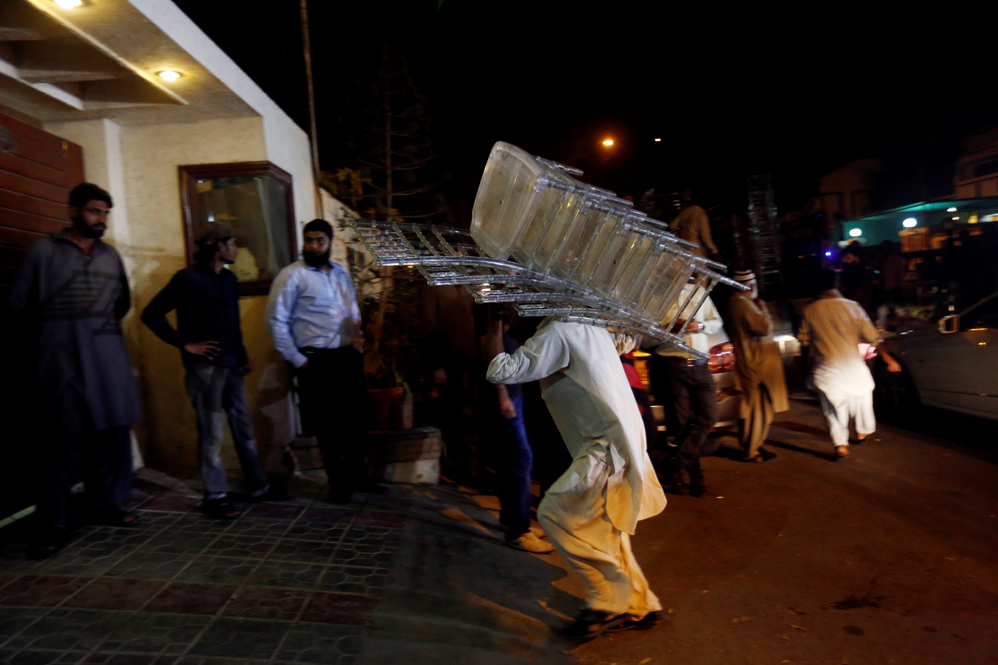 A worker carries in chairs as relatives gather outside the residence of Junaid Jamshed, pop star turned evangelical Muslim cleric, in Karachi, Pakistan December 7, 2016. REUTERS/Akhtar Soomro