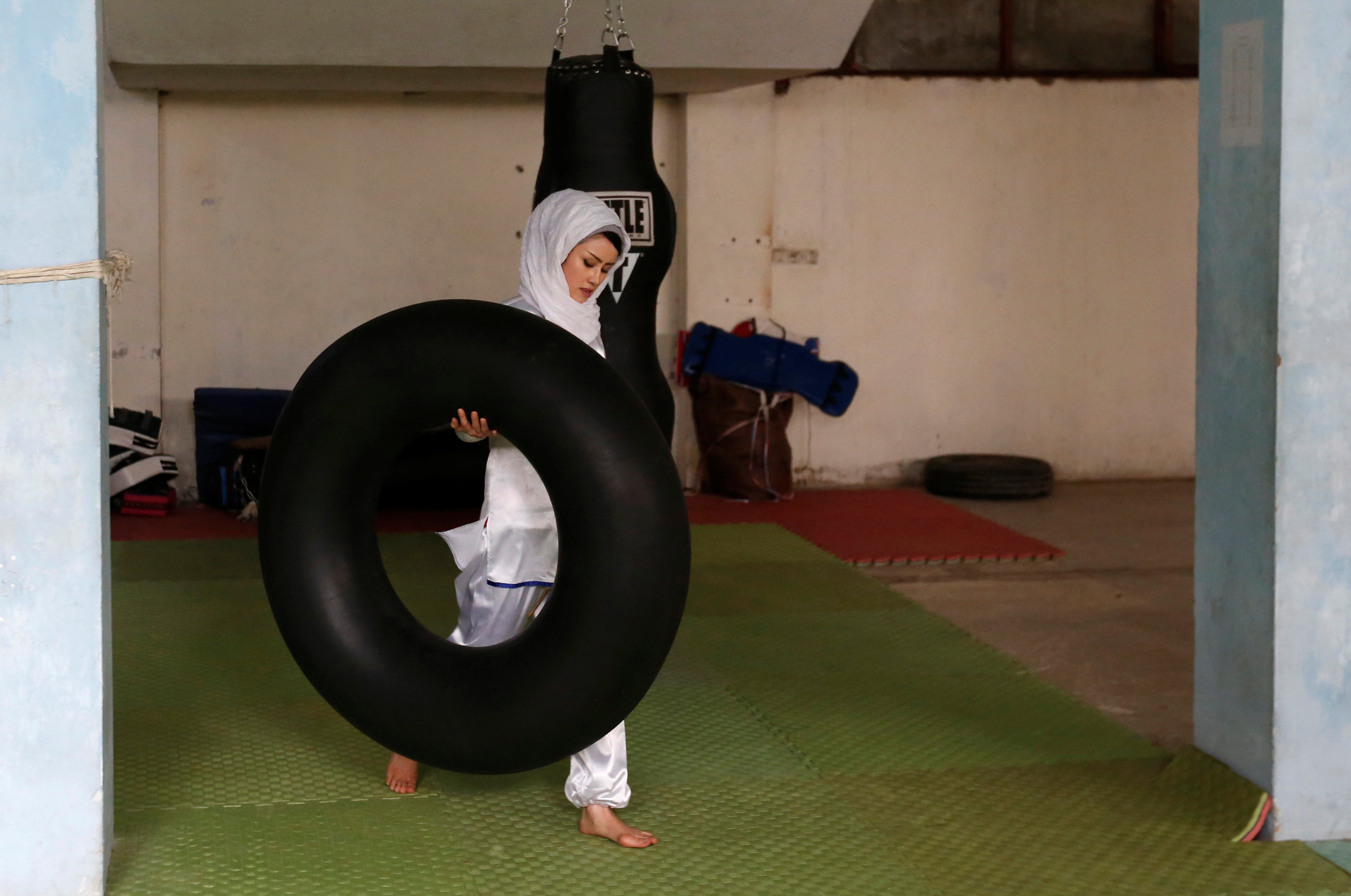 Sabera Bayanne, 20, a student at the Shaolin Wushu club, carries a tube before an exercise in Kabul, Afghanistan January 29, 2017. REUTERS/Mohammad Ismail