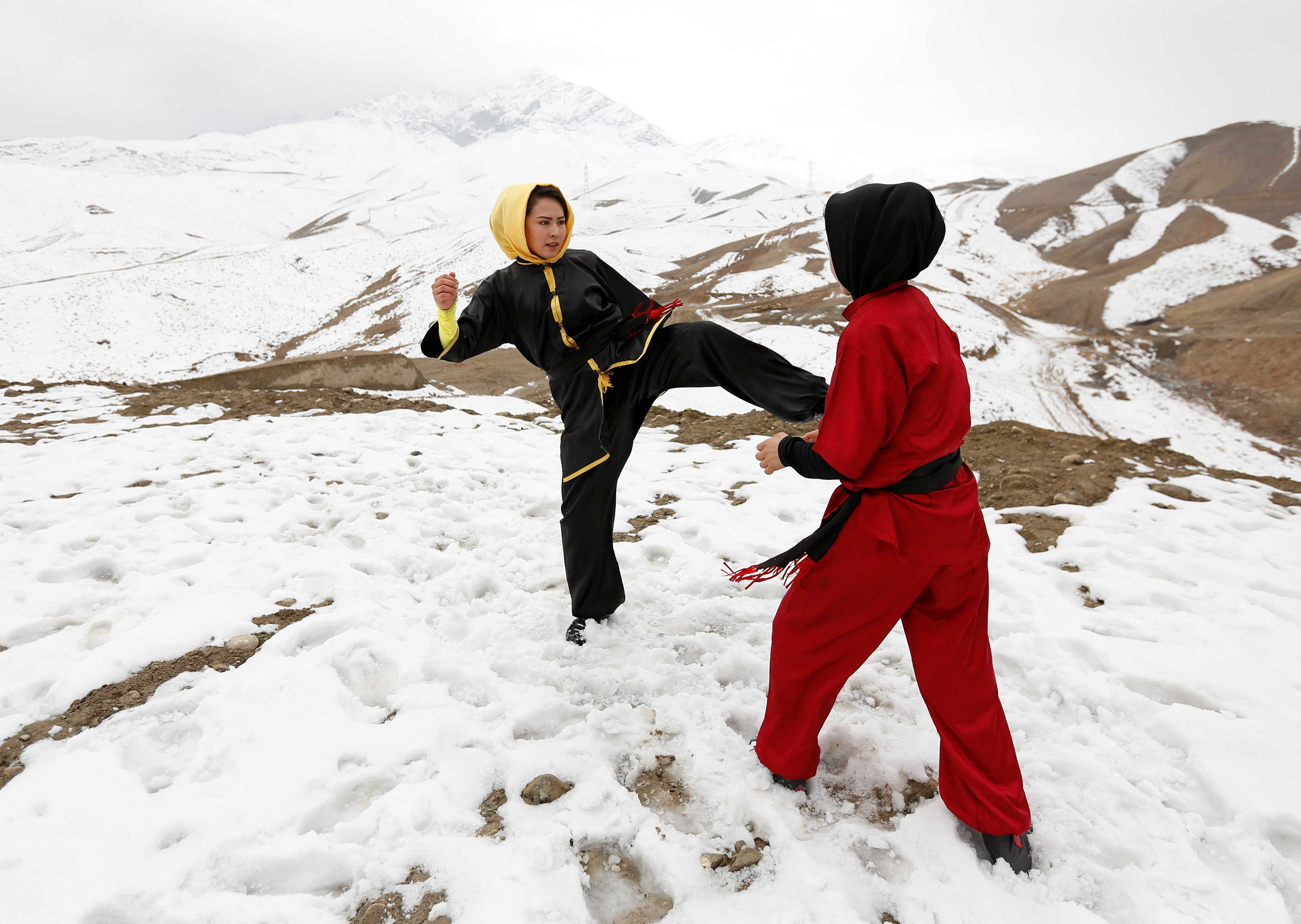 Sima Azimi (L), 20, a trainer at the Shaolin Wushu club, and Shakila Muradi, 18, show their Wushu skills to other students on a hilltop in Kabul, Afghanistan January 29, 2017. REUTERS/Mohammad Ismail