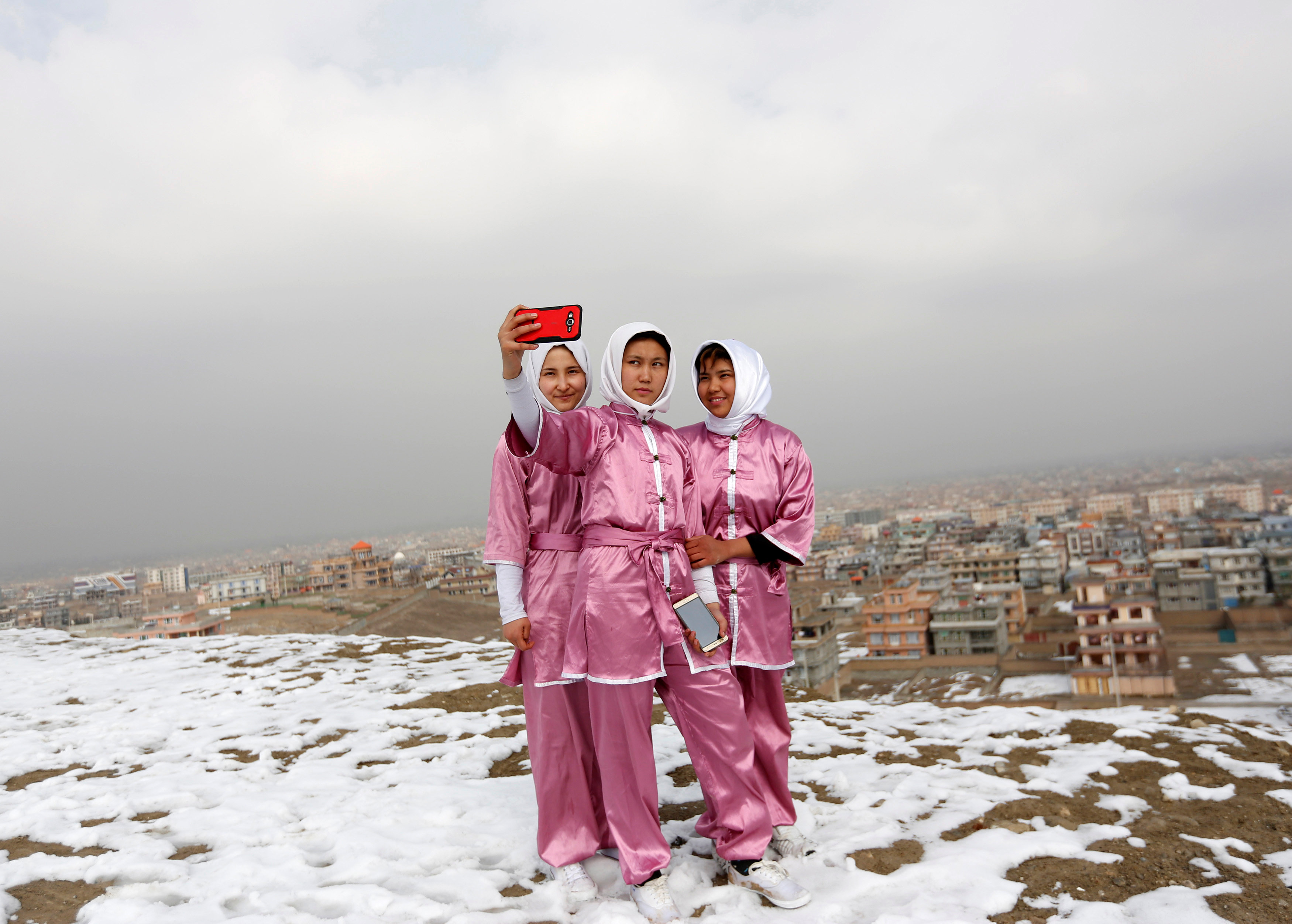 Latifa Safay (R), 15, Hanifa Doosti (C), 17, and Suraya Rezai, 19, students of the Shaolin Wushu club, take a selfie before practicing on a hilltop in Kabul, Afghanistan January 29, 2017. REUTERS/Mohammad Ismail