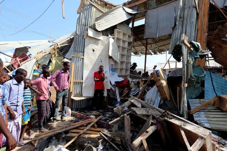 Traders look at a stall destroyed at the scene of a suicide bomb explosion at the Wadajir market in Madina district of Somalia's capital Mogadishu February 19, 2017. REUTERS/Feisal Omar