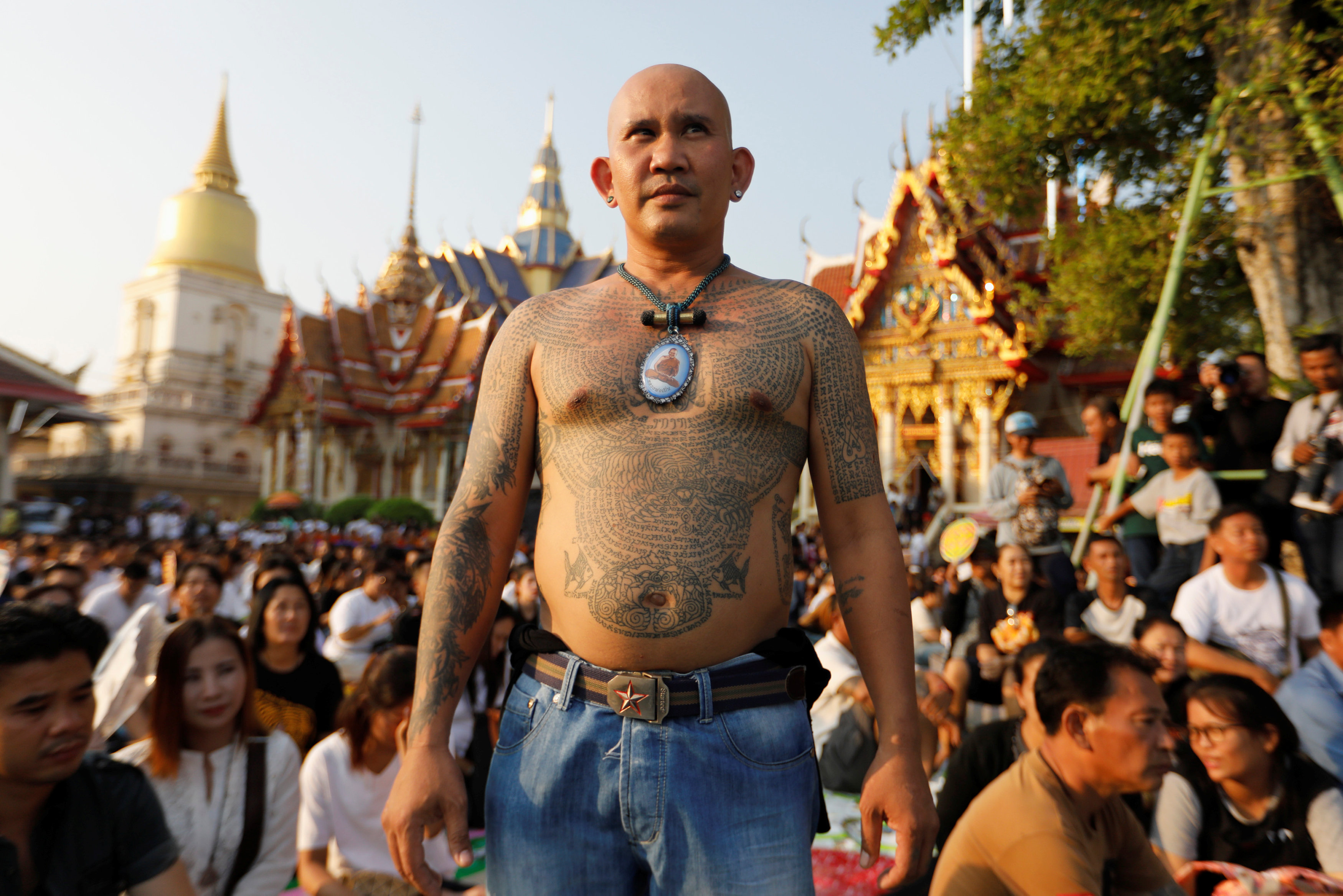 A devotee attends a religious tattoo festival at Wat Bang Phra, where devotees come to recharge the power of their sacred tattoos, in Nakhon Pathom province, Thailand, March 11, 2017. REUTERS/Jorge Silva