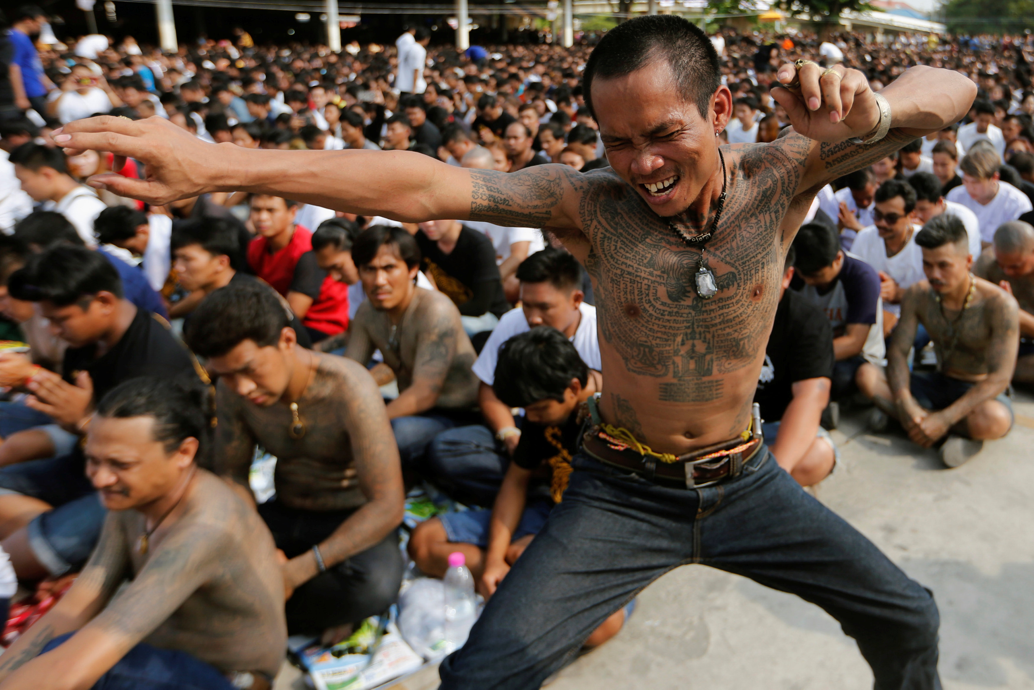 A devotee in trance mimics a beast during a religious tattoo festival at Wat Bang Phra, where devotees come to recharge the power of their sacred tattoos, in Nakhon Pathom province, Thailand, March 11, 2017. REUTERS/Jorge Silva