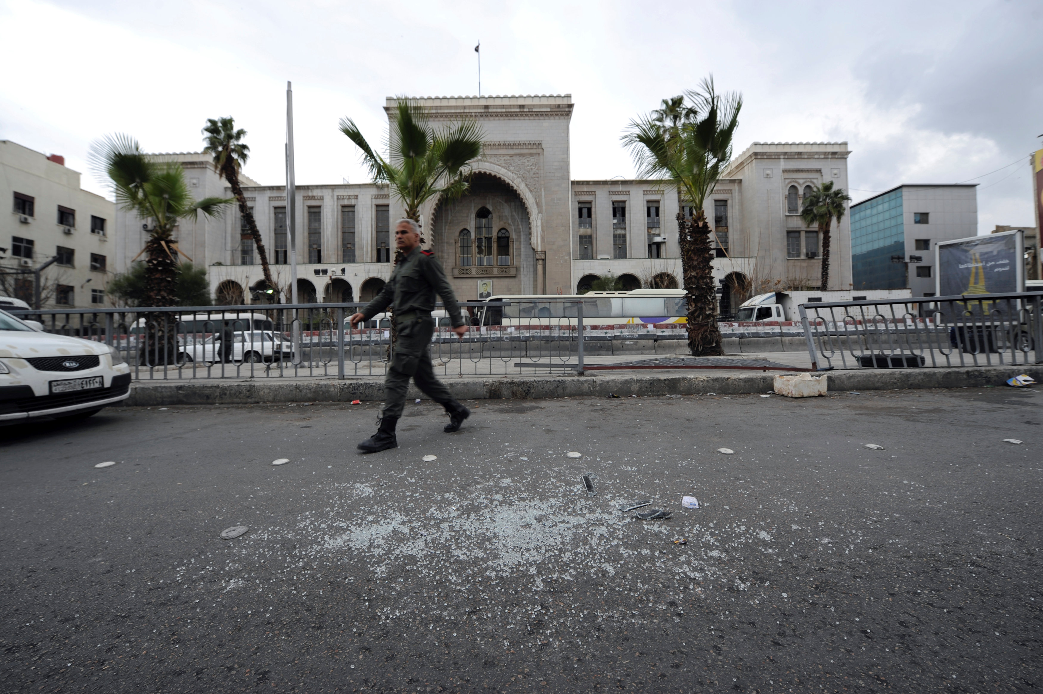 A Syrian security personnel walks near broken glass after a suicide blast at the Palace of Justice in Damascus, Syria March 15, 2017. REUTERS/Omar Sanadiki
