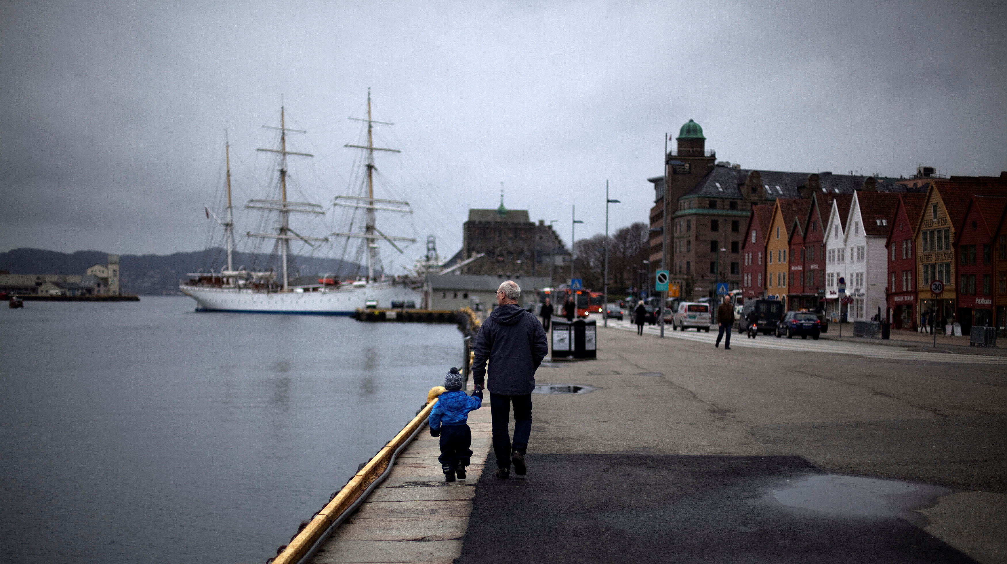 FILE PHOTO -  A man walks with a child near the marina in downtown Bergen, southwestern Norway, March 20, 2012.  REUTERS/Stoyan Nenov/File Photo