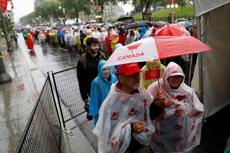 Despite the rain, people wait in a security line to enter Parliament Hill during Canada Day celebrations as the country marks its 150th anniversary since Confederation, in Ottawa, Ontario, Canada July 1, 2017. REUTERS/Blair Gable