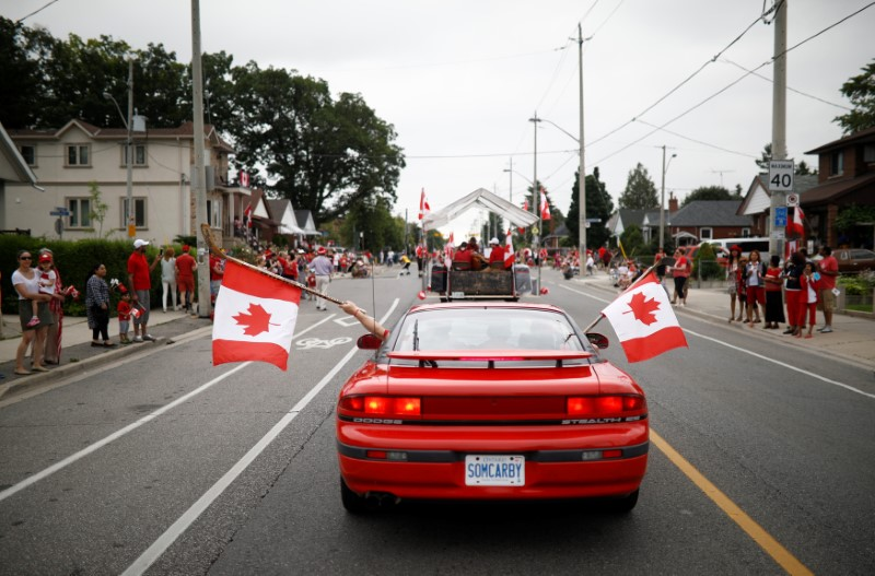 """People hold Canadian flags with hockey sticks from inside a car during the East York Toronto Canada Day parade, as the country marks its 150th anniversary with """"Canada 150"""" celebrations, in Toronto, Ontario, Canada July 1, 2017.    REUTERS/Mark Blinch      TPX IMAGES OF THE DAY"""
