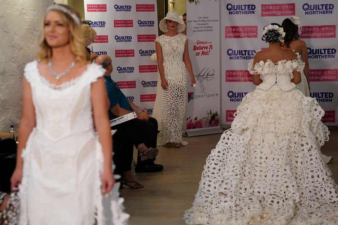 Models present wedding dresses made out of toilet paper during a fashion show. REUTERS/Carlo Allegri