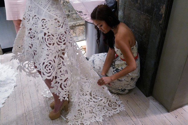 A designer is pictured backstage fixing a wedding dress made out of toilet paper before a fashion show. REUTERS/Carlo Allegri