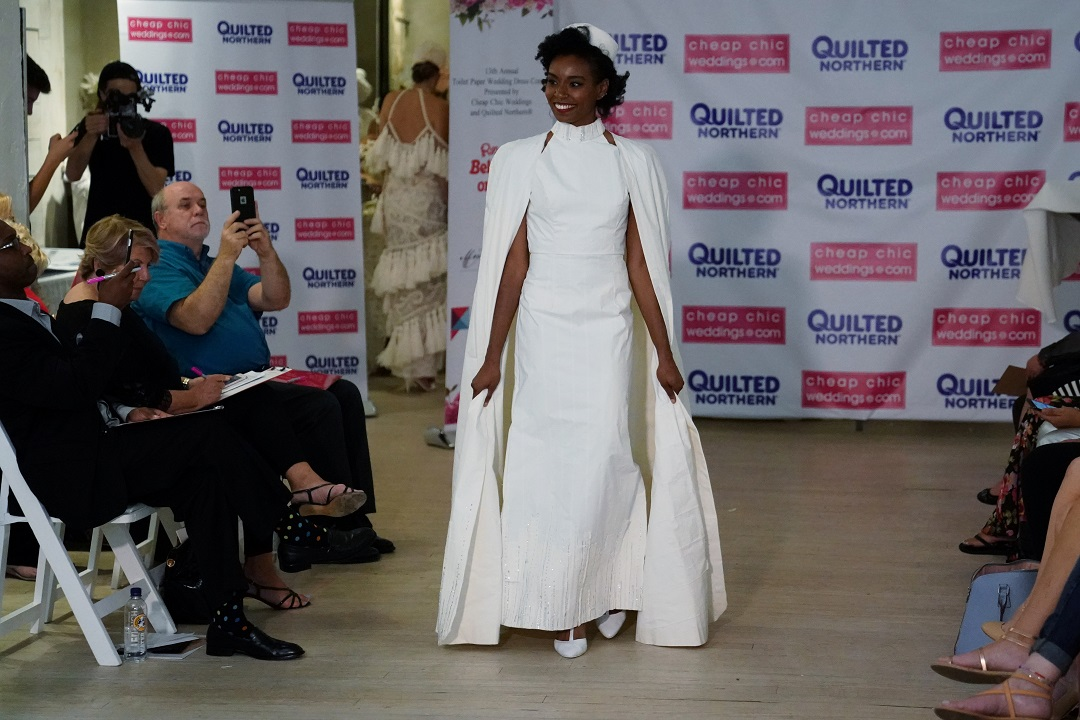 A model presents a wedding dress made out of toilet paper during a fashion show. REUTERS/Carlo Allegri