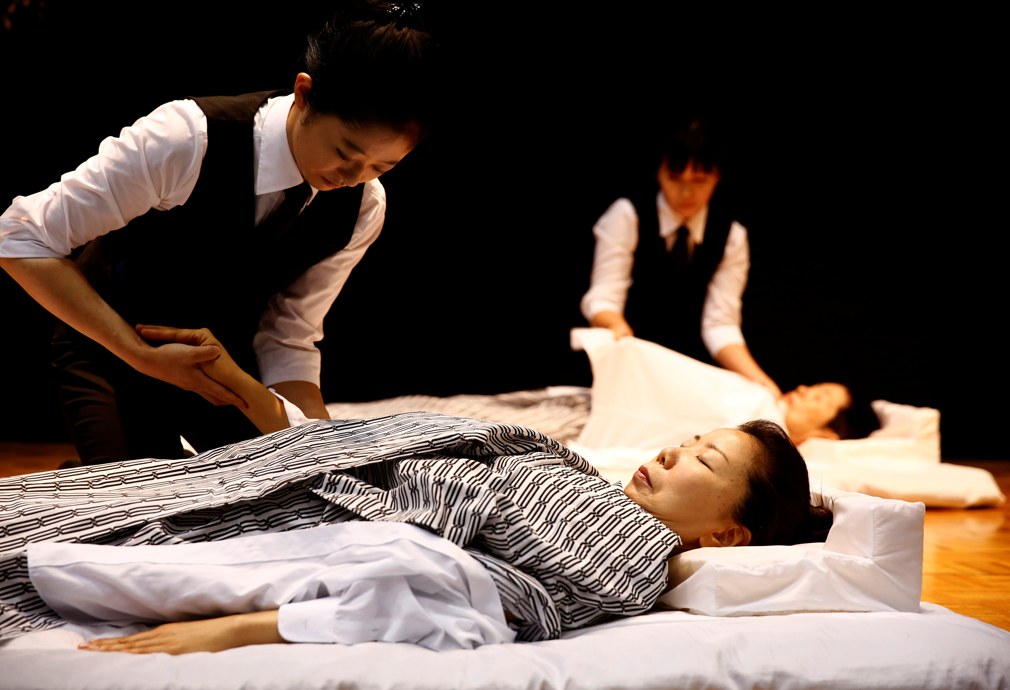 Funeral undertakers change clothes on models during an encoffinment competition at Life Ending Industry EXPO 2017 in Tokyo, Japan August 24, 2017 REUTERS/Kim Kyung-Hoon