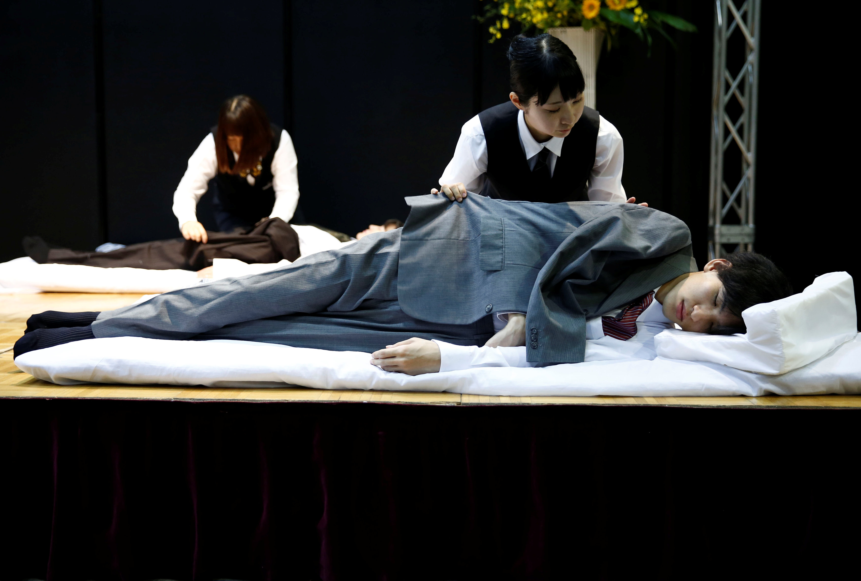 Funeral undertakers dress models during an encoffinment competition at Life Ending Industry EXPO 2017 in Tokyo, Japan August 24, 2017. REUTERS/Kim Kyung-Hoon
