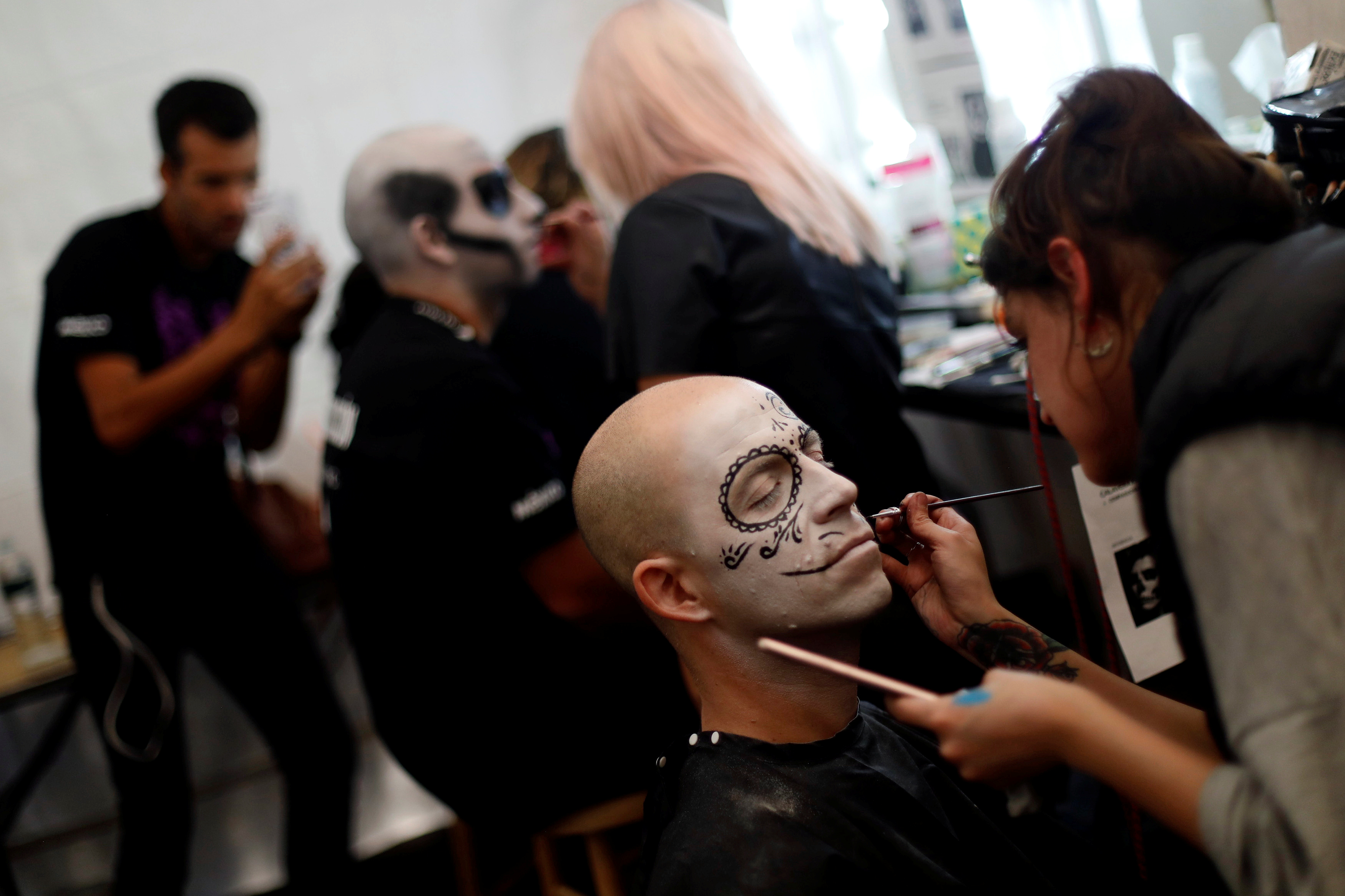 A man gets a make-up before taking part in a procession to commemorate Day of the Dead in Mexico City, Mexico, October 28, 2017. REUTERS/Edgard Garrido