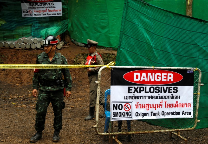 A police officer and soldier stand guard in front of Tham Luang cave complex, where 12 schoolboys and their soccer coach are trapped inside a flooded cave, after Thailand's government instructed members of the media to move out urgently, in the northern province of Chiang Rai, Thailand, July 8, 2018. REUTERS/Soe Zeya Tun