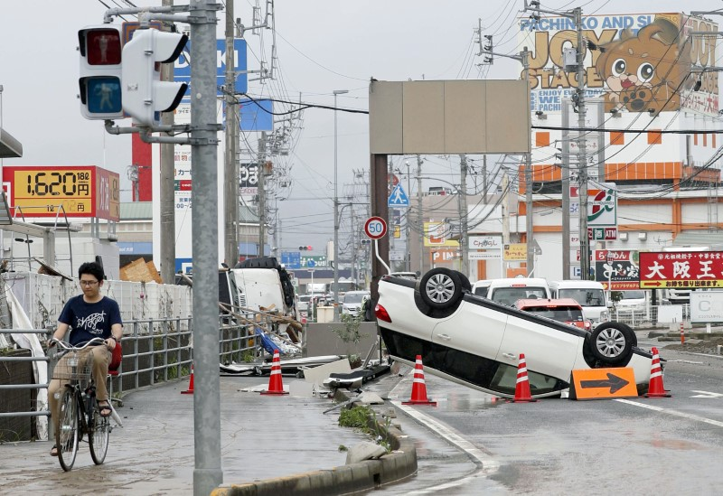 An overturned car remains on a street after heavy rain in Ozu, Ehime Prefecture, Japan, in this photo taken by Kyodo July 8, 2018. Mandatory credit  Kyodo/via REUTERS