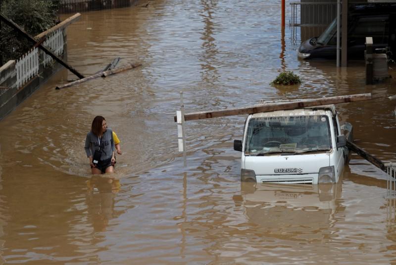 Women make their way in a flooded area in Mabi town in Kurashiki, Okayama Prefecture, Japan, July 8, 2018. REUTERS/Issei Kato