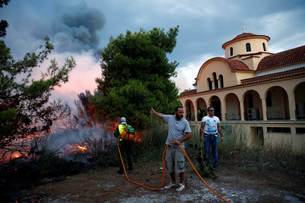 People try to extinguish a wildfire burning next to a church in the town of Rafina, near Athens, Greece, July 23, 2018. REUTERS/Costas Baltas