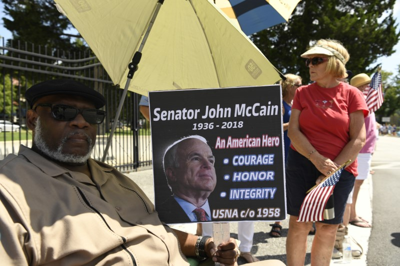 Aug 12, 2018; Annapolis, MD, USA; Charles James Sr. sits with a sign he made to watch the passing of John McCain's motorcade on his way to be laid to rest at the U.S. Naval Academy. Mandatory Credit: Jasper Colt via USA TODAY NETWORK