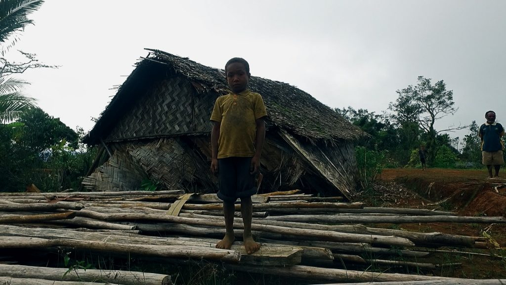 Photo credit: EMTEK 'Last Mile' Documentary: Homes destroyed - A young child stands in front of what is left of his home.