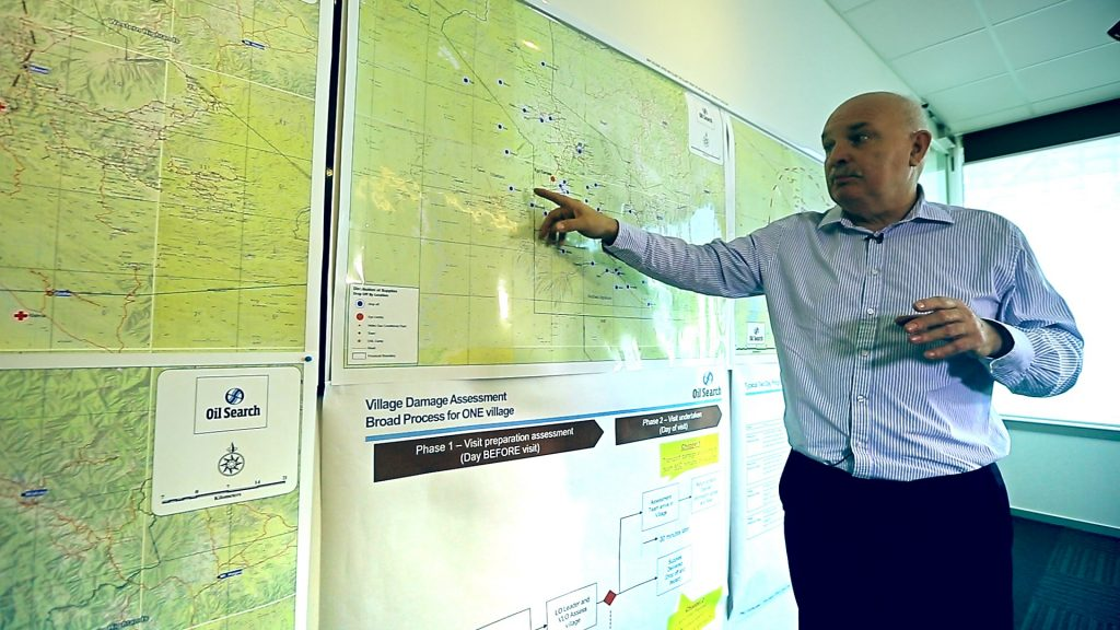Photo credit: EMTEK 'Last Mile' Documentary: Location map - Oil Search Managing Director, Peter Botten assessing a map for disaster relief.