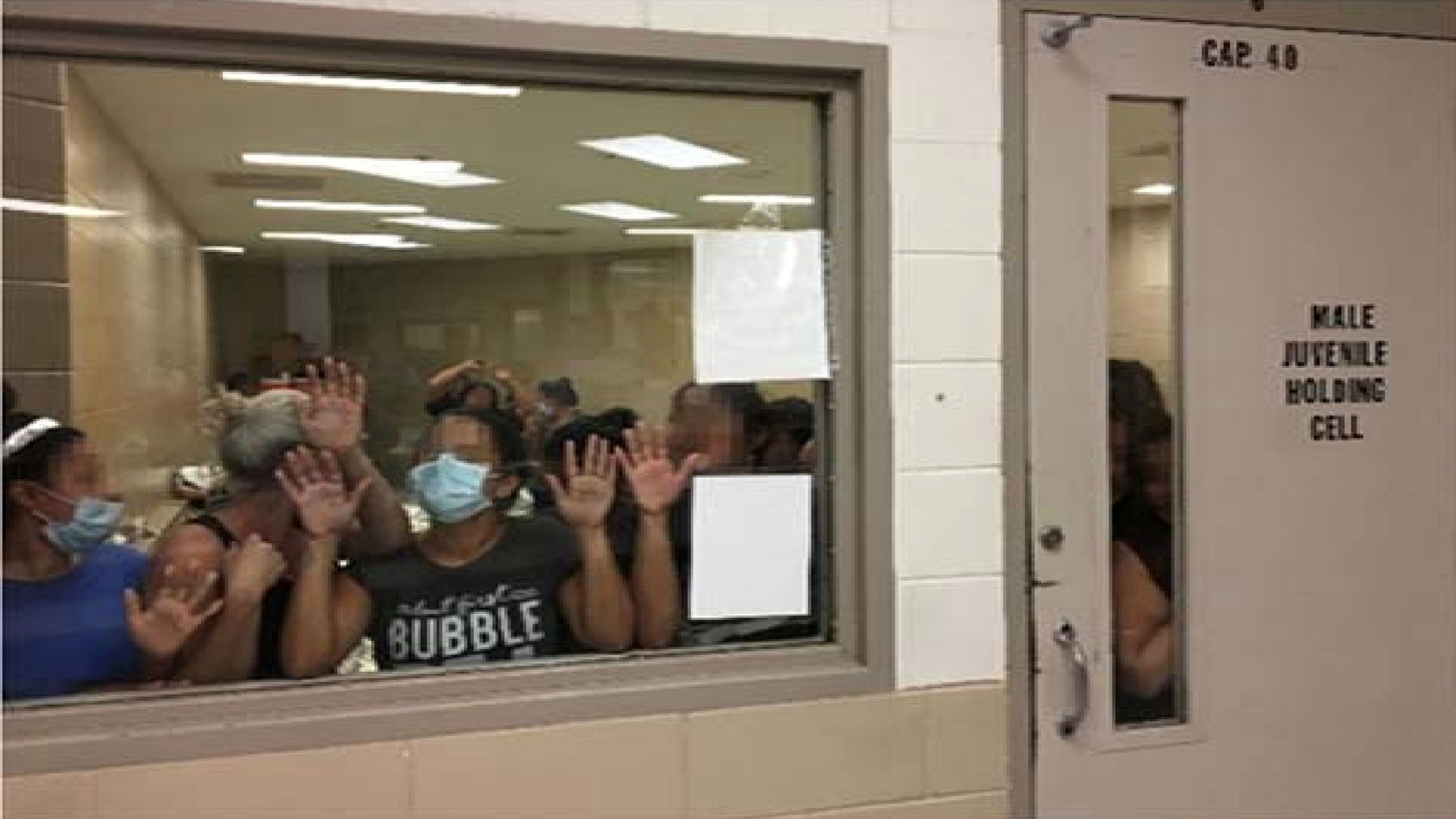Some of a group of 51 adult females press against the window of a cell built to hold 40 male juveniles at Fort Brown Border Patrol station in a still image from video in Brownsville, Texas, U.S. on June 12, 2019 and released as part of a report by the Department of Homeland Security's Office of Inspector General on July 2, 2019. Picture pixelated at source. Office of Inspector General/DHS/Handout via REUTERS