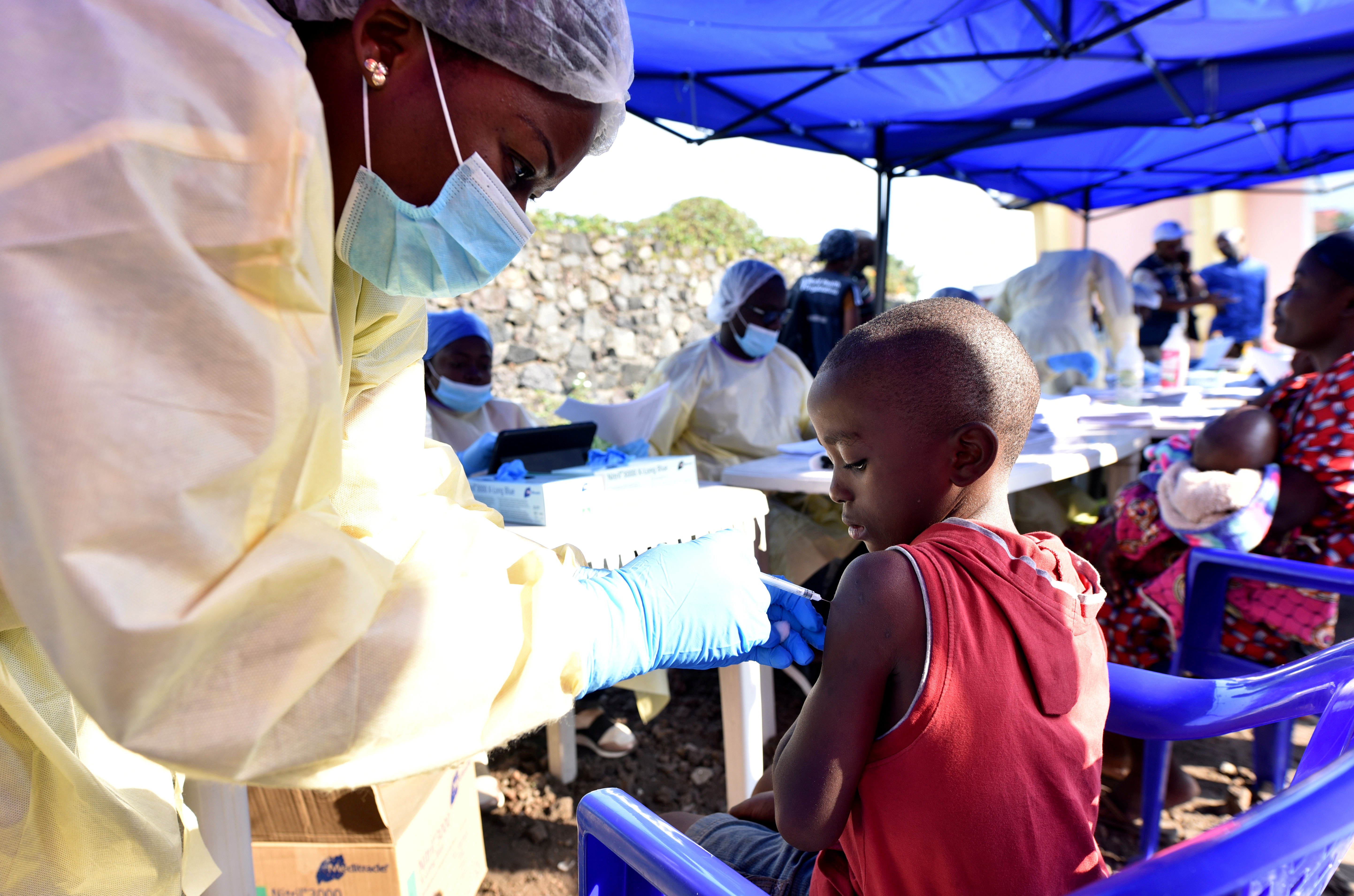 FILE PHOTO: A Congolese health worker administers ebola vaccine to a child at the Himbi Health Centre in Goma, Democratic Republic of Congo, July 17, 2019. REUTERS/Olivia Acland/File Photo
