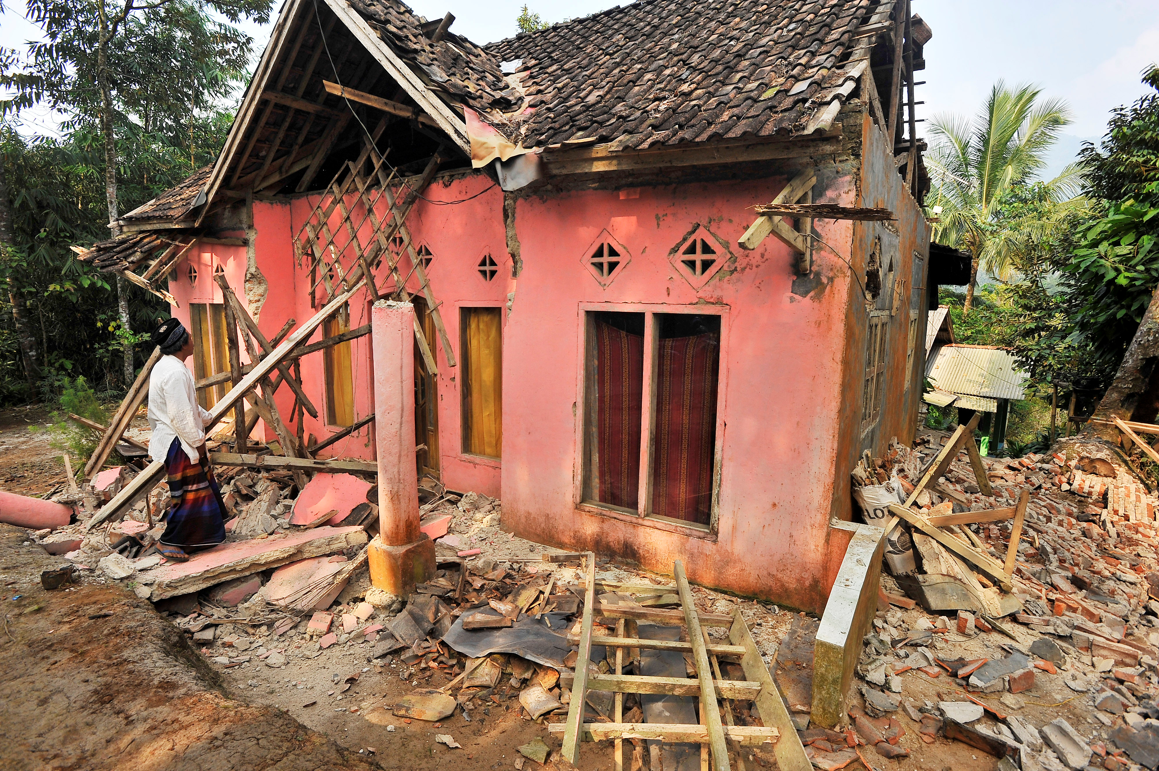A man examines his house damaged after an earthquake hit in Pandeglang, Banten province, Indonesia, August 3, 2019.  Antara Foto/Asep Fathulrahman/ via REUTERS