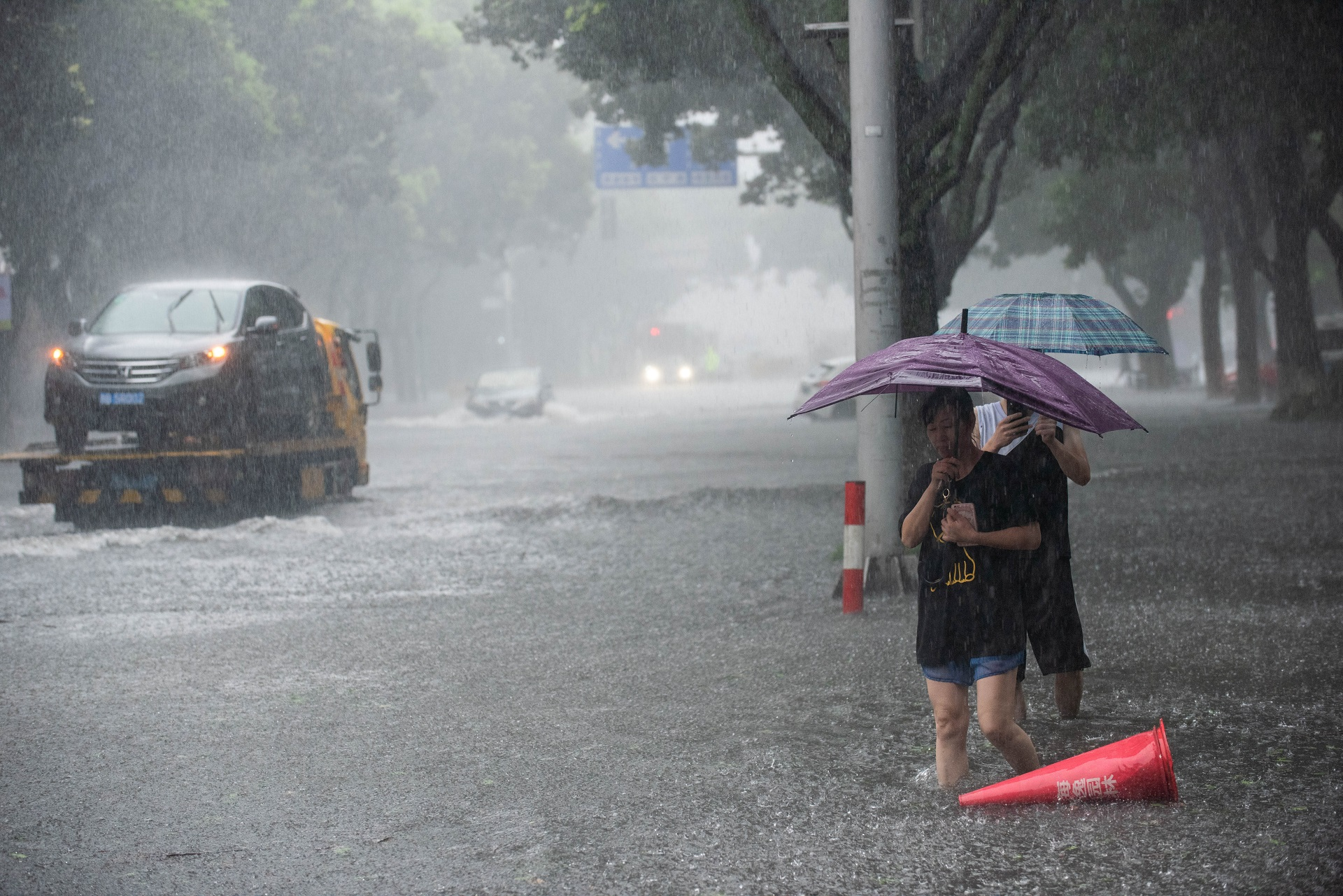 People holding umbrellas wade through floodwaters amid heavy rainfall on a street after super typhoon Lekima made landfall in Ningbo, Zhejiang province, China August 10, 2019.  REUTERS/Stringer