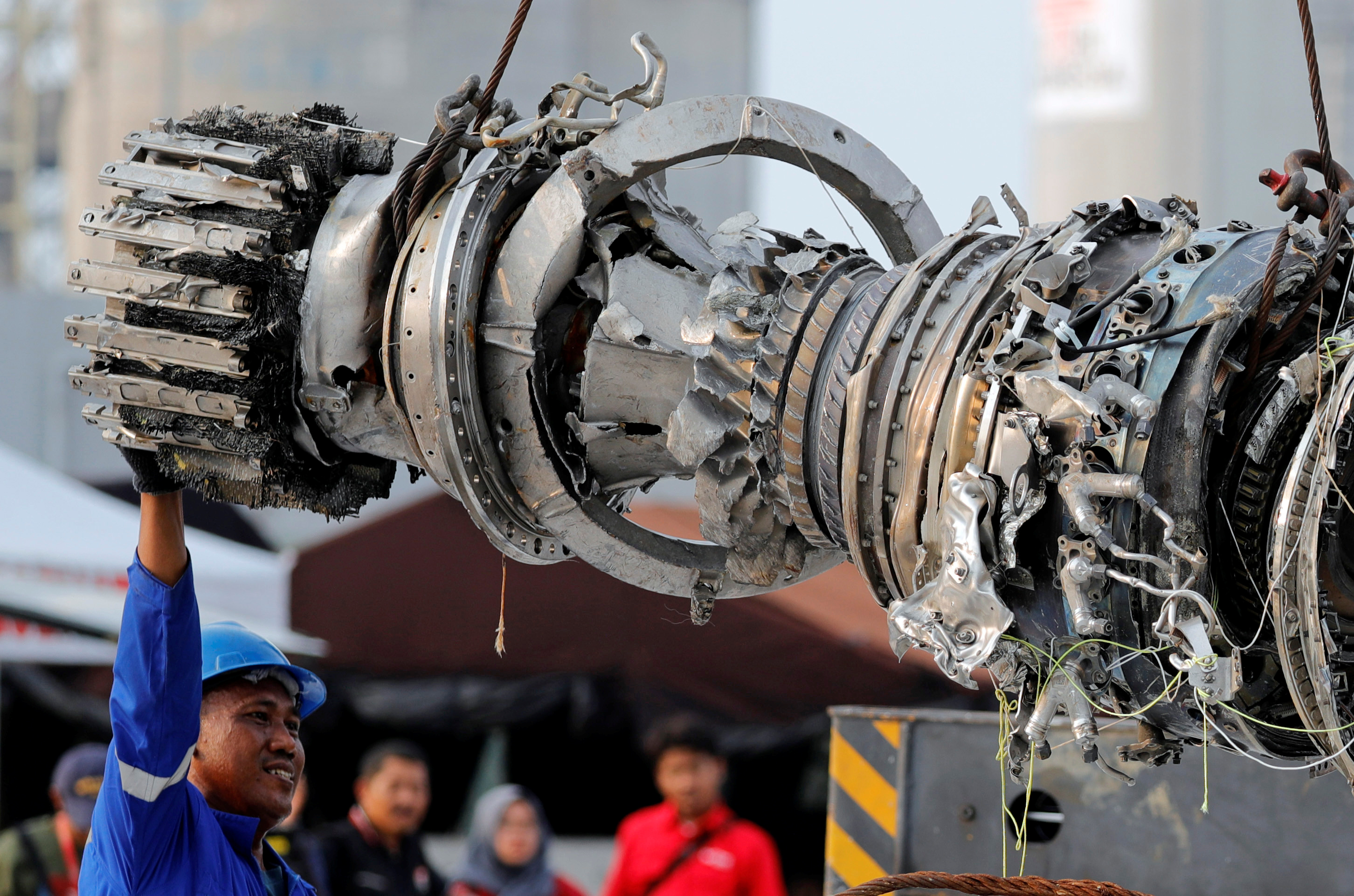 FILE PHOTO: A worker assists his colleague during the lifting of a turbine engine of the Lion Air flight JT610 jet, at Tanjung Priok port in Jakarta, Indonesia, November 4, 2018.  REUTERS/Beawiharta