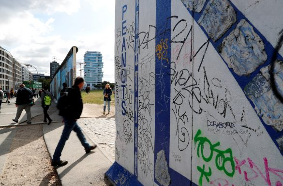 FILE PHOTO: A pedestrian walks past segments of the East Side Gallery, the largest remaining part of the former Berlin Wall, in Berlin, Germany, September 19, 2019. REUTERS/Fabrizio Bensch/File Photo