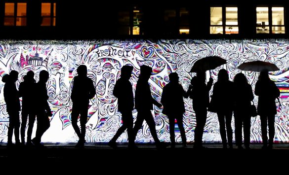 People stand in front of a projection on the East Side Gallery, the largest remaining part of the former Berlin Wall, in Berlin, Germany, November 4, 2019. On November 9th Germany will mark the 30th anniversary of the fall of the Berlin Wall (Berliner Mauer) in 1989. REUTERS/Fabrizio Bensch